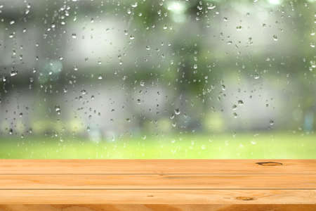 Empty wooden table over water drop on window garden background. Ready for product display montage.の写真素材