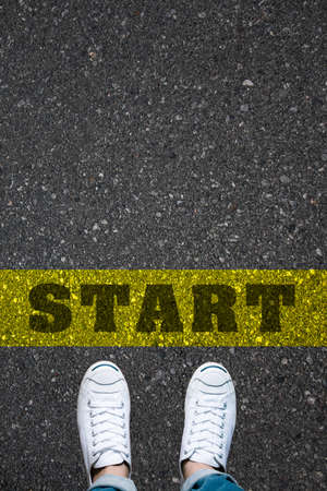 Photo pour Pair of shoes standing on a road with the word START on the yellow background - image libre de droit