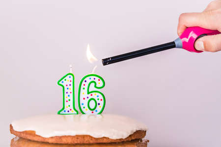 Man lighting sixteenth birthday candles on cake