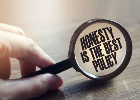 Photo pour Honesty Is The Best Policy Messageunder magnifying glass in hand. Marketing business concept. - image libre de droit
