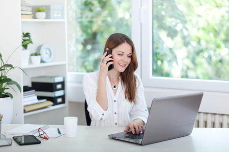 Photo for Beautiful young woman working on computer and talking on phone - Royalty Free Image