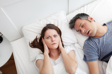 Photo pour Woman covering ears, annoyed by the snoring of her husband - image libre de droit