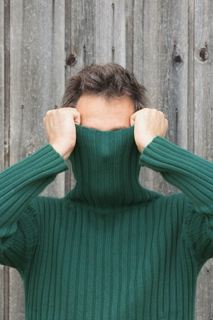 Man pulling turtleneck over his face