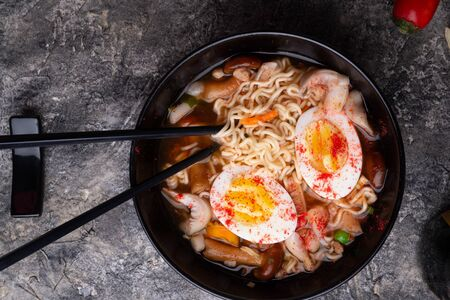 Photo pour spicy instant noodles soup with shrimps, egg and  mushrooms. served  by black chopsticks. flat lay - image libre de droit