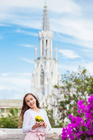 Photo pour Beautiful young girl on the Ortiz Bridge eating a mango in front of the famous gothic church of La Ermita built on 1602 in the city of Cali in Colombia - image libre de droit