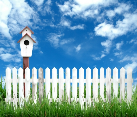 birdhouse with white fenceand blue sky