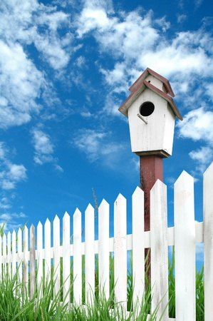 white fence with birdhouse and blue sky
