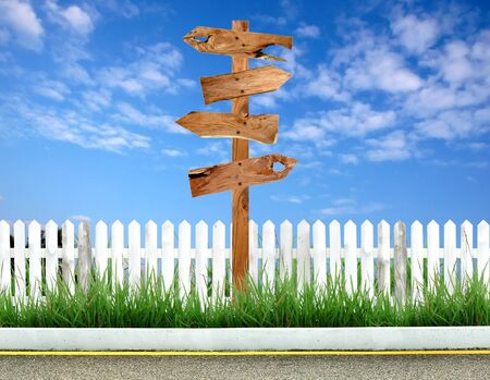 wooden signpost with white fence and blue sky