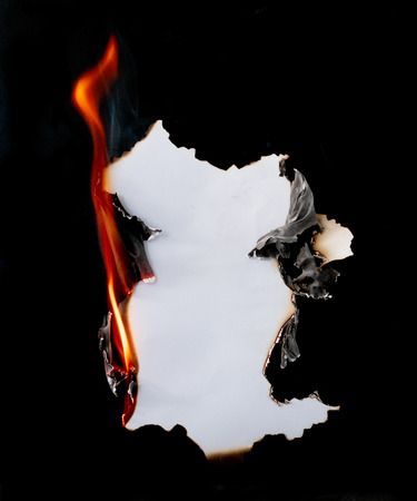 Photo for burning piece of  paper on black background - Royalty Free Image