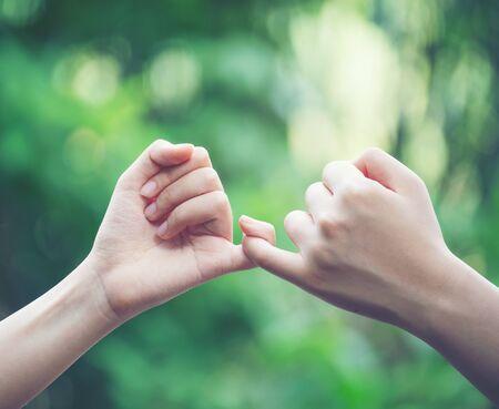 Foto de hands hook each other's little finger on nature background, concept of promise - Imagen libre de derechos
