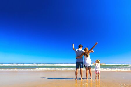 Photo pour Happy father mother and little stand on the sea shore on a sunny day.COpy space, back view. - image libre de droit