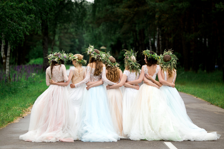 Photo pour Wedding. The bride in a white dress standing and embracing bridesmaids - image libre de droit