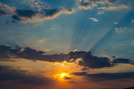 Photo pour Colorful sunset in the blue sky.The rays of the sun breaking through the dark clouds. Abstract natural background. Beautiful nature - image libre de droit
