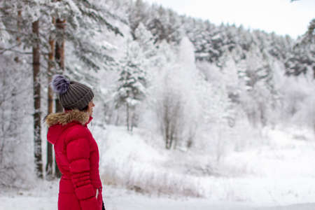 Photo pour A young woman in a red jacket in a winter forest. Winter and frosty forest in the mountains. Nature walk - image libre de droit