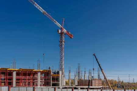 Photo pour Construction of a mall cranes on a background of blue summer sky - image libre de droit