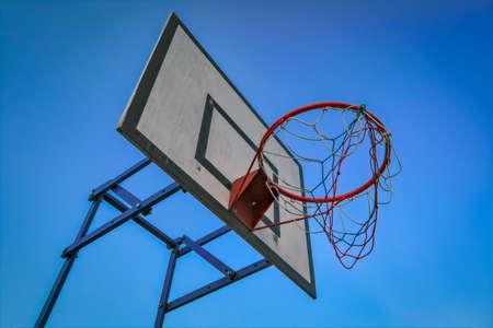 Basketball basket on blue sky background. Basketball basket and board on the blue sky background. Basketball hoop and backboard against blue sky