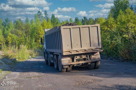 Photo pour Lorry dump truck rides on a dirt road against the background of the forest and blue sky. - image libre de droit