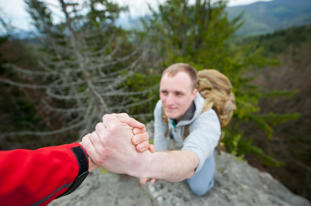 Close-up of helping hand, hiking help each other. Focus on hands. People teamwork climbing or hiking with motivation and inspiration. Wide angle lens