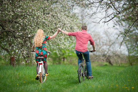 Active couple ride bicycles in the spring garden back to camera and holding hands. Woman with long blond hair wearing flowered dress and man in a red shirtの写真素材