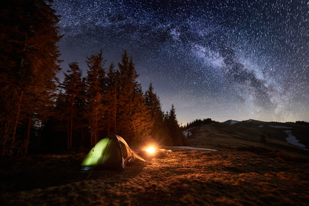 Photo pour Night camping. Illuminated tent and campfire near forest under beautiful night sky full of stars and milky way - image libre de droit
