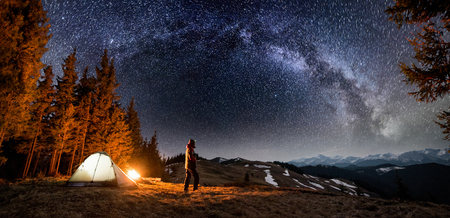 Foto de Male tourist have a rest in his camp near the forest at night. Man standing near campfire and tent under beautiful night sky full of stars and milky way, and enjoying night scene. Panoramic landscape - Imagen libre de derechos