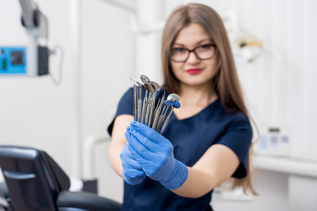 Woman dentist with blue gloves holding tools - dental mirrors and dental sondes at the dental office. Close-up, selective focus on tools. Dentistry