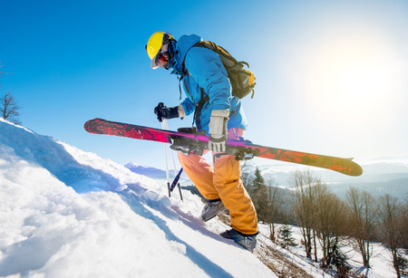 Male skier walking up the snowy hill in the Carpathians mountains carrying his skis copyspace seasonal activity sport sportsman hobby recreation travel concept