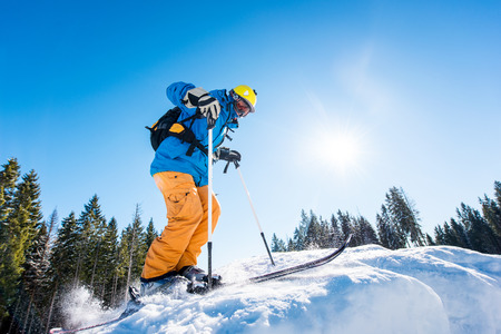 Low angle shot of a skier riding down the slope at ski resort mountains copyspace seasonal activity sport sportsman hobby recreation travel concept