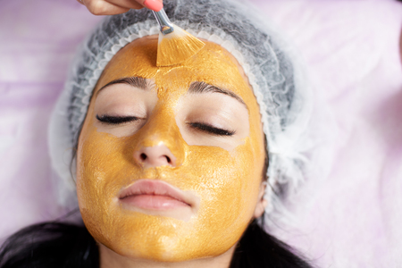 Photo pour Face closeup of a female client of a beauty salon with a gold mask on. Cosmetology and skin care routine. - image libre de droit