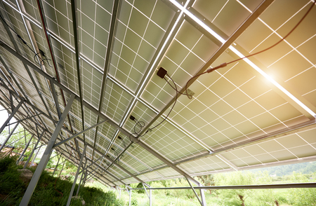 Photo pour Interior of stand-alone photo voltaic solar system secured on metal rear legs on green grass, lit by summer sun. Alternative energy, environment protection and cheap electricity production concept. - image libre de droit