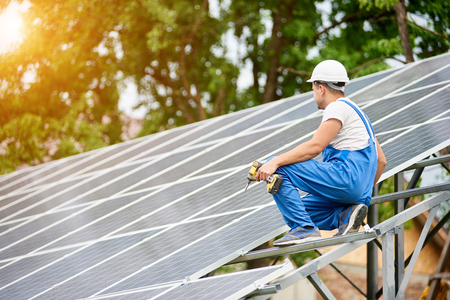 Construction worker with screwdriver connecting photo voltaic panels on solar system shiny surface background. Alternative energy, ecology protection and cheap electricity production concept.