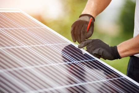 Photo pour Close-up technicians hands in protective gloves making mark with pencil on metal platform for installing solar photo voltaic panel on blurred green summer background. - image libre de droit