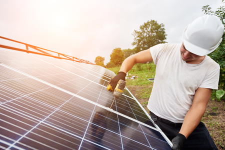 Photo for Professional technician working with screwdriver connecting solar photo voltaic panel to exterior metal platform under clear blue sky. Alternative renewable ecological green energy concept. - Royalty Free Image
