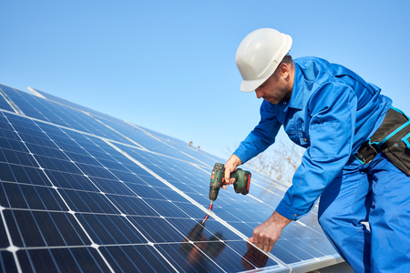 Photo pour Man worker in blue suit and protective helmet installing solar photovoltaic panel system using screwdriver. Professional electrician mounting blue solar module. Alternative energy ecological concept. - image libre de droit