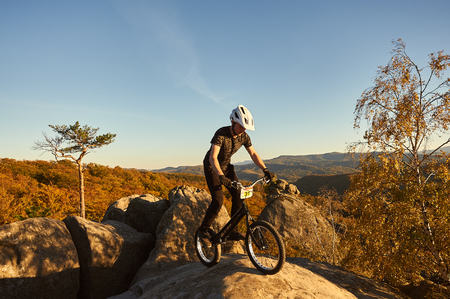 Young male cyclist balancing on trial bicycle on top of big boulder, rider making acrobatic stunt on summer evening, blue sky and forest on background. Concept of extreme sport active lifestyle