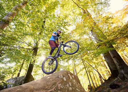 Foto de Professional cyclist balancing on back wheel on trial bike, man rider making acrobatic stunt on the edge of big boulder in the forest on summer sunny day. Concept of extreme sport active lifestyle - Imagen libre de derechos