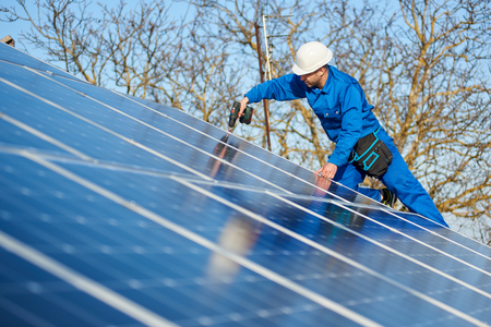 Foto de Man engineer in blue suit and protective helmet installing stand-alone solar photovoltaic panel system using screwdriver. Professional electrician mounting blue solar module on roof of modern house. - Imagen libre de derechos
