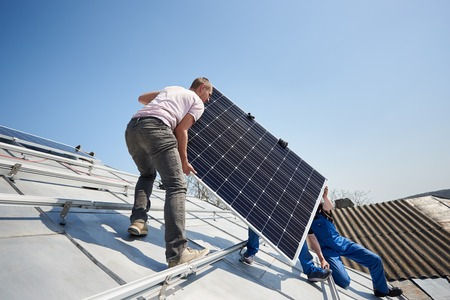 Photo for Male workers installing stand-alone solar photovoltaic panel system. Electricians lifting blue solar module on roof of modern house. Alternative energy sustainable resources renewable concept. - Royalty Free Image