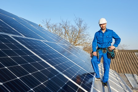 Photo pour Smiling engineer in blue suit and protective helmet installing solar photovoltaic panel system using screwdriver. Electrician standing on roof of modern house. Alternative energy ecological concept. - image libre de droit
