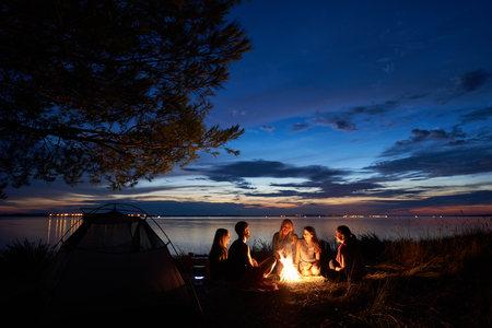 Foto de Night summer camping on lake shore. Group of five young happy tourists sitting in high grass around bonfire near tent under beautiful blue evening sky. Tourism, friendship and beauty of nature concept - Imagen libre de derechos