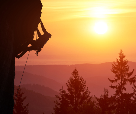 Photo pour Snapshot of silhouette of male climber with copy space. Beautiful landscape with trees, mountain peaks and sunshine on orange sky on background. Over filtered. Mountain rock climbing concept. - image libre de droit