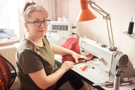 Foto de Female tailor in glasses sitting on her workplace in atelier, turning back and smiling while working for garment repairing. Sewing-machine, table lamp, ruler, scissors, pins and threads on background. - Imagen libre de derechos
