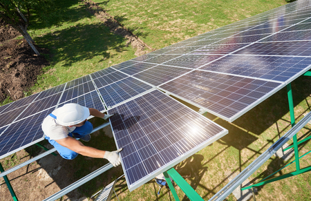 Photo for Professional worker installing solar panels on the green metal construction, using different equipment, wearing helmet. Innovative solution for energy solving. Use renewable resources. Green energy. - Royalty Free Image