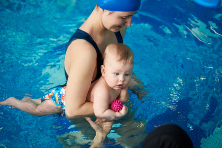 Photo pour Mother teaching small boy swimming. Child first visiting swimming pool. Young woman helping her baby staying on blue clear water. Healthy family lifestyle concept. Top angle view - image libre de droit