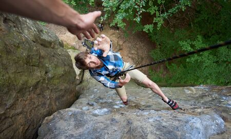 Photo for Guy climber hanging on rope between rocks, pulling up his hand to his friend to ask him for help. Man helping his friend to climb on cliff. Top view. Business, teamwork, success, goal, help concept. - Royalty Free Image