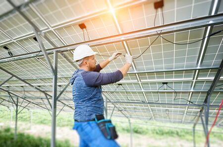 Photo pour Young electrician connecting electrical cables inside the lit by sun solar modules. Installing and wiring of solar photo voltaic panel system. Alternative energy and profitable investment concept. - image libre de droit