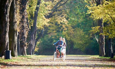 Foto de Young tourist couple, handsome bearded man and attractive blond long-haired woman cycling together tandem double red bike by sunny alley with golden leaves on tall trees background in the autumn - Imagen libre de derechos