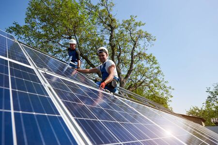 Photo pour Two technicians sitting on metal platform installing heavy solar photo voltaic panel on blue sky and green tree background. Stand-alone solar panel system installation and professionalism concept. - image libre de droit