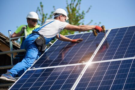 Photo for Two workers technicians installing heavy solar photo voltaic panels to high steel platform. Exterior solar system installation, alternative renewable green energy generation concept. - Royalty Free Image