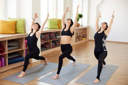 Photo for Fit adult women practicing yoga poses in fitness class. Group of healthy strong female doing fit exercises in white gym. Health care and lifestyle. Yoga masters demonstrate High lunge and Warrior pose - Royalty Free Image